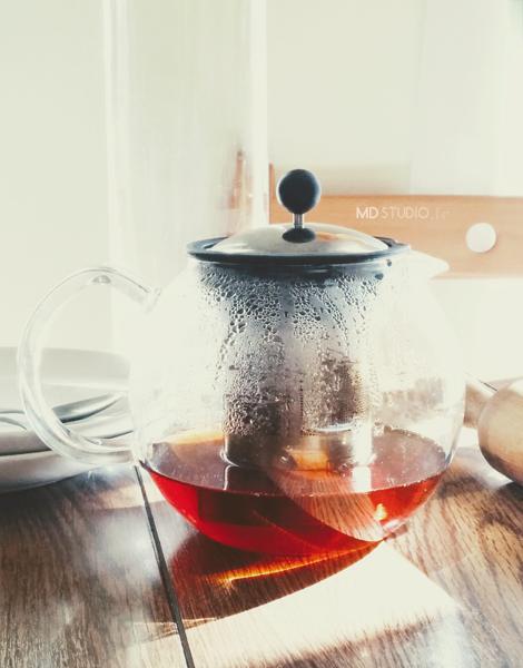 lumière se reflétant sur le thé et à travers le verre d'une théière